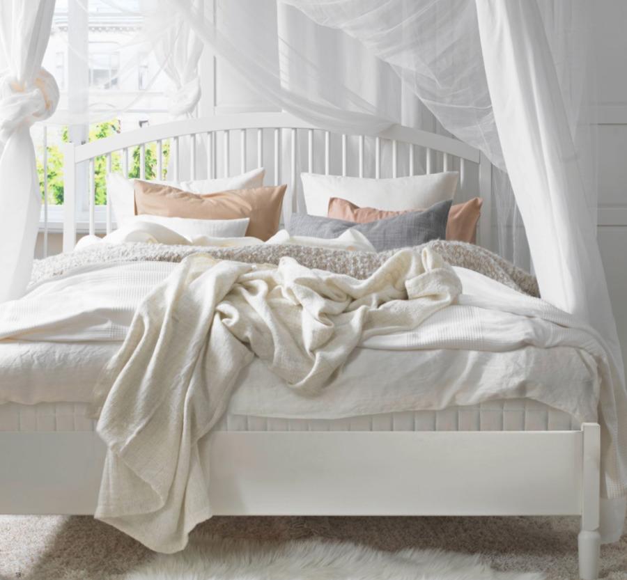 Dormitorio con cama de madera blanca y dosel de IKEA