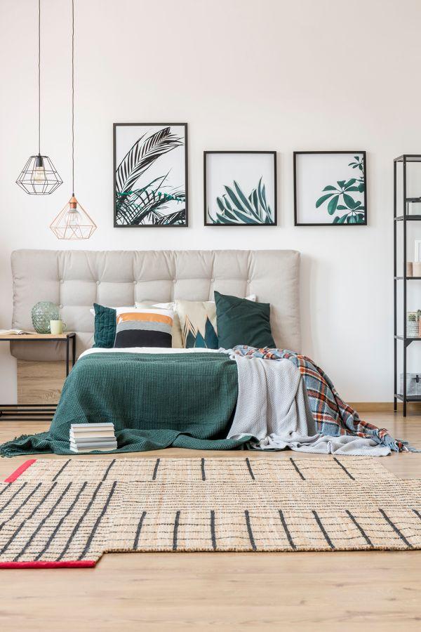 Dormitorio con cama y cabecero y cuadros