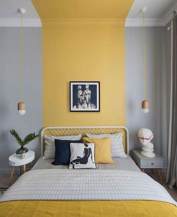 Dormitorio con gran pared amarilla y gris
