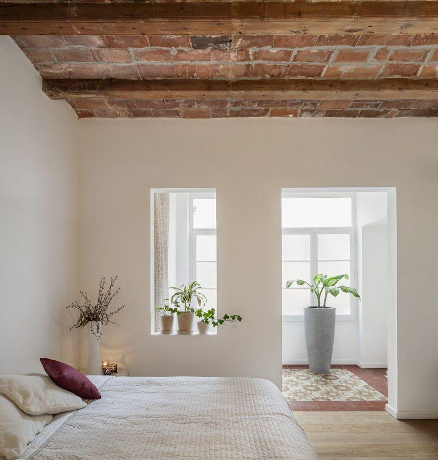 Dormitorio con ladrillo en techo