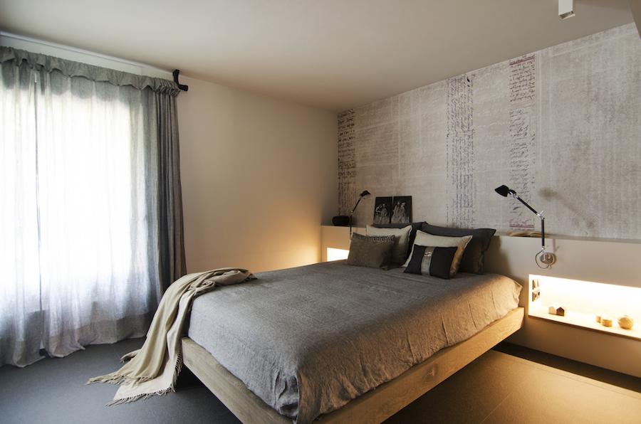 Dormitorio con muro a media altura de pladur y luz integrada en hornacionas