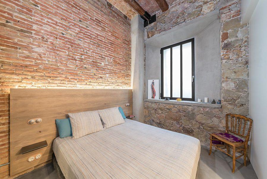 Dormitorio con muros de ladrillo visto