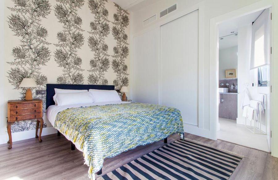 Dormitorio con papel pintado con motivos florales y baño en suite
