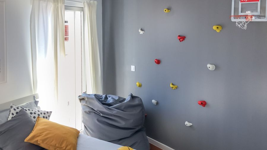 Dormitorio con pared con rocódromo