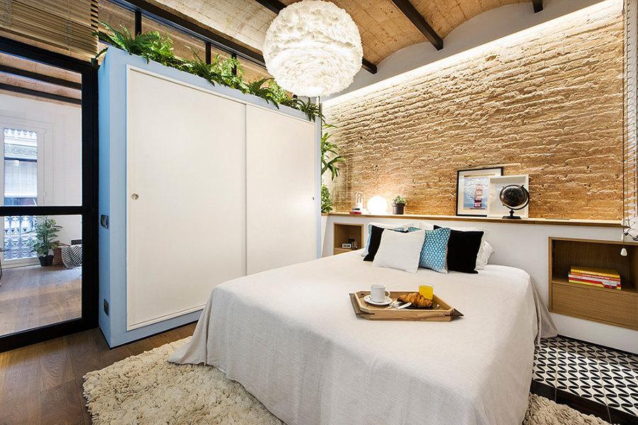 Dormitorio con pared de ladrillo original y bovedilla catalana