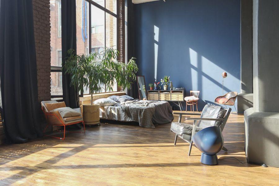 Dormitorio con pared en azul y grandes ventanales