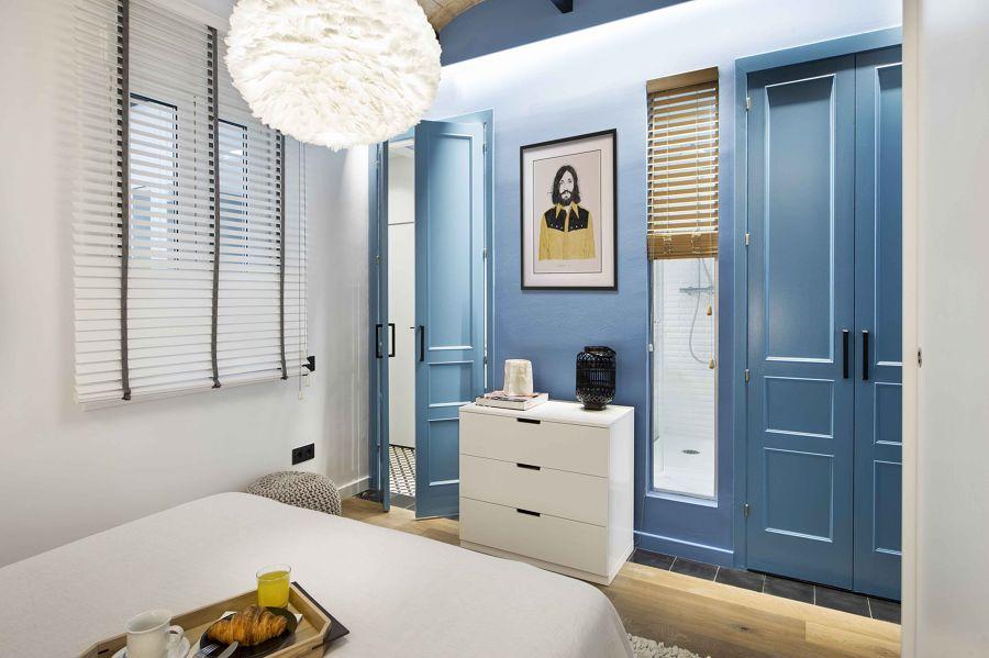 Dormitorio con puertas y pared de color azul