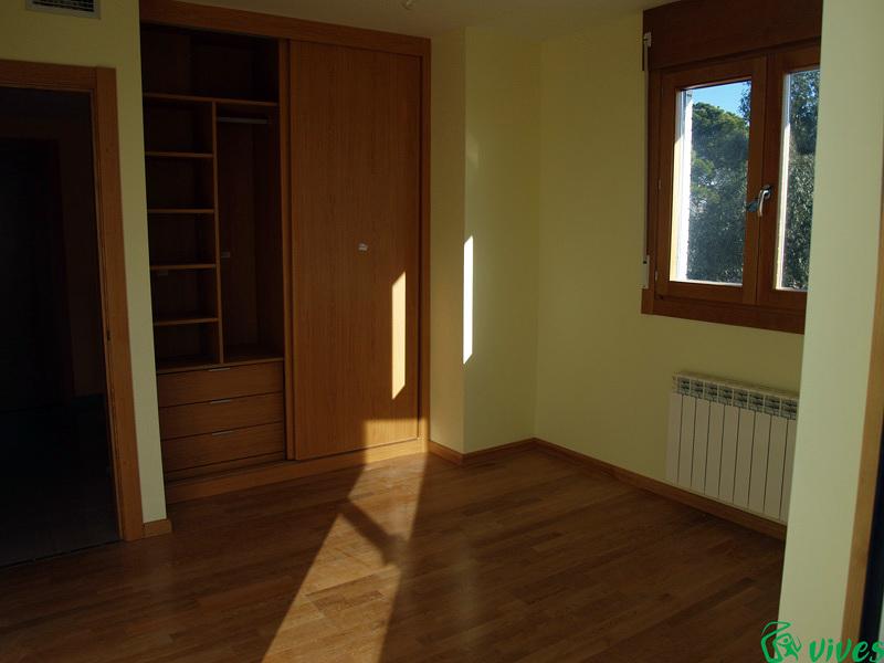 Dormitorio con suelos de tarima y terraza propia del adosado