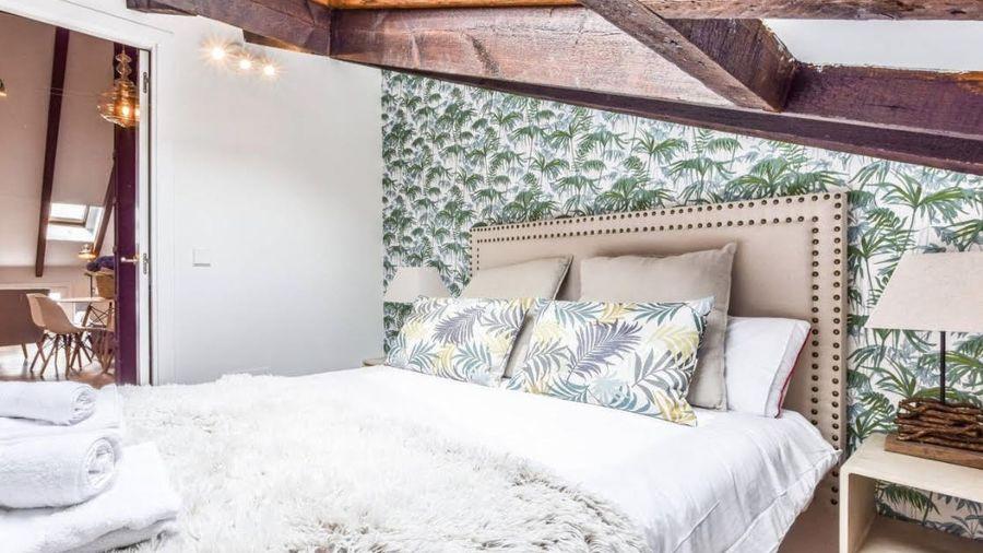 Dormitorio con techo abuhardillado y cabecero piel