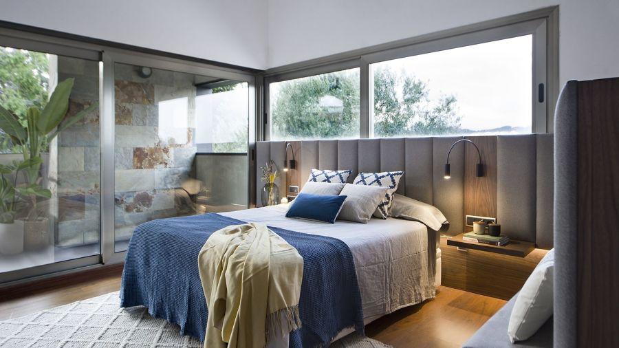 Dormitorio con ventanas en la pared del cabecero y mobilario a medida.