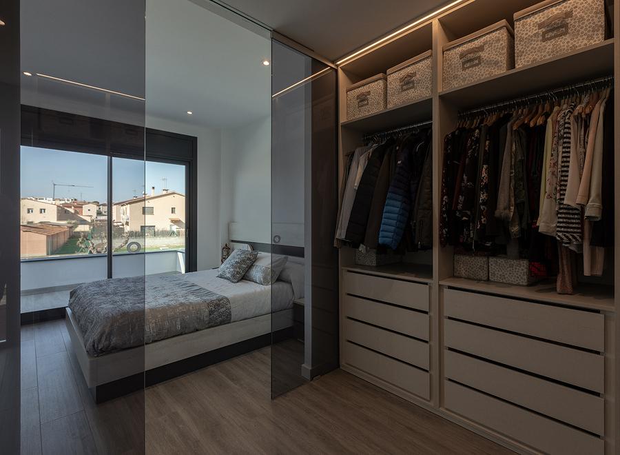 Dormitorio con vestidor abierto tras puertas de cristal ahumado