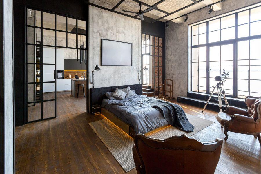 Dormitorio de estilo industrial con grandes techos