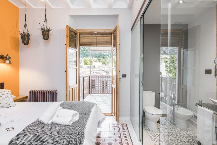 Dormitorio de estilo rústico y ventanas de madera