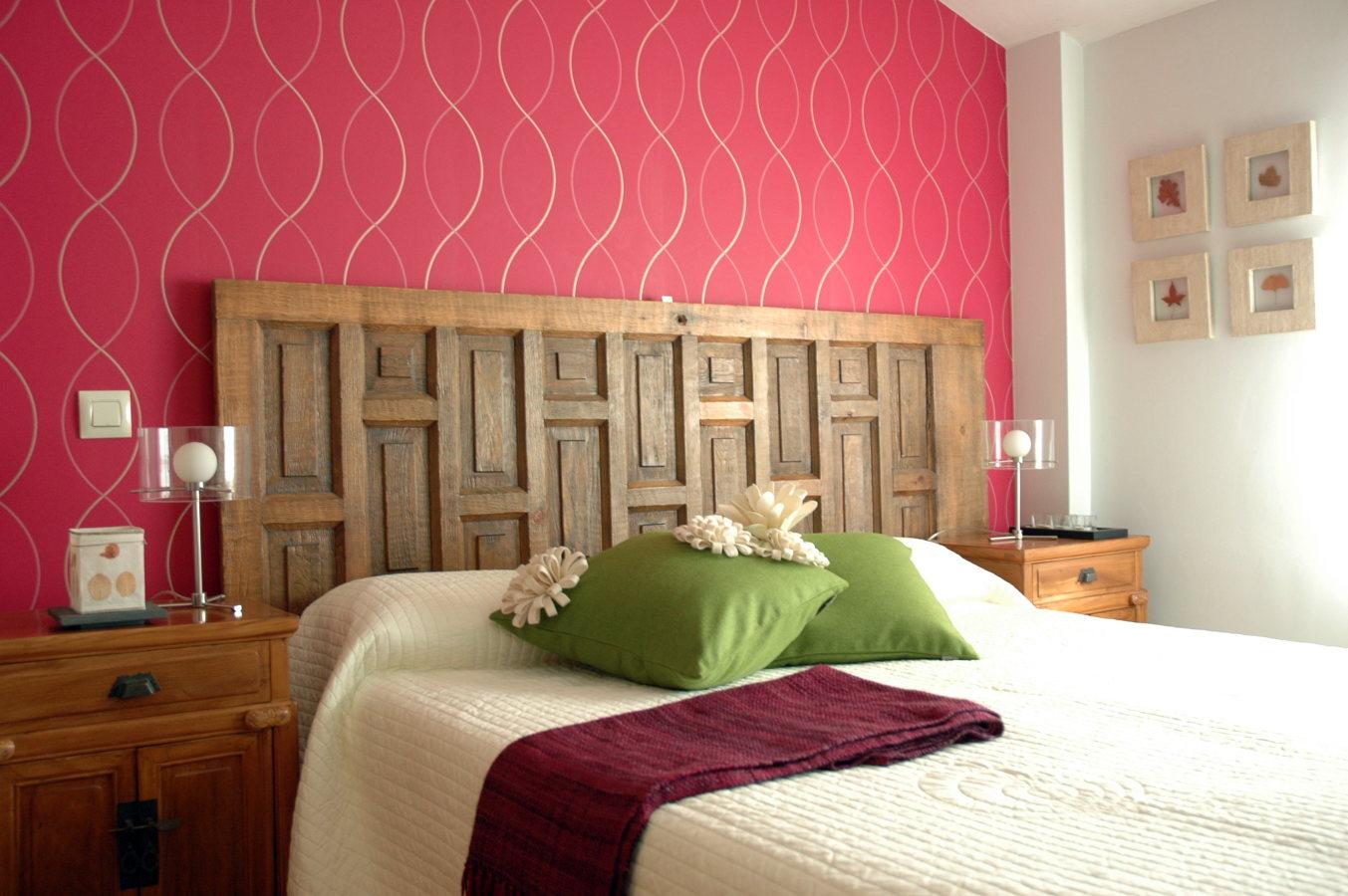 Dormitorio decorado con puerta recuperada como cabecero..
