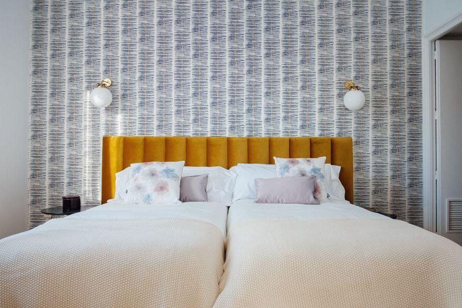 Dormitorio ecléctico con papel pintado