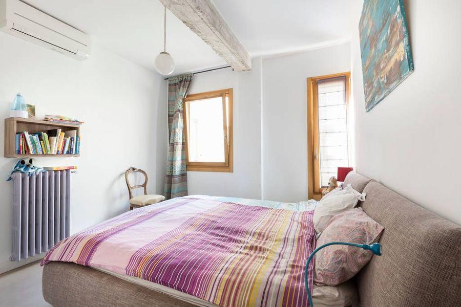 Dormitorio ecléctico con split a/a y radiador de hierro.
