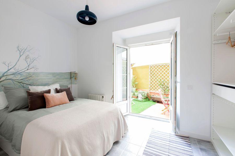 Dormitorio en tonos blancos con terraza