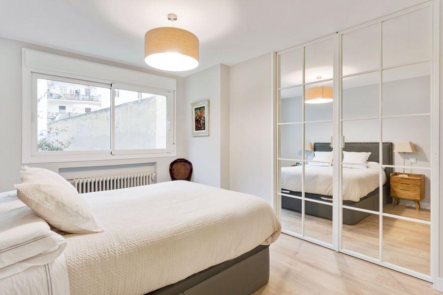 Dormitorio moderno con armario espejo empotrado