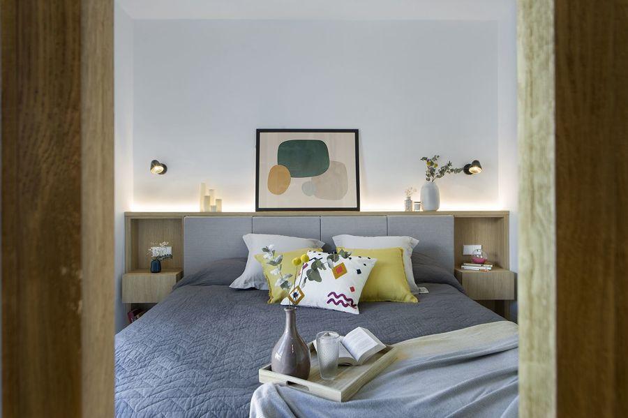 Dormitorio moderno con cabecero de madera a medida y detalles en gris y azul