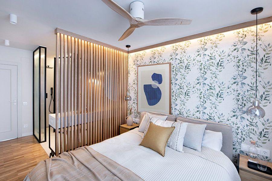 Dormitorio moderno con papel pintado con motivos botánicos, ventilador de techo y LEDs.