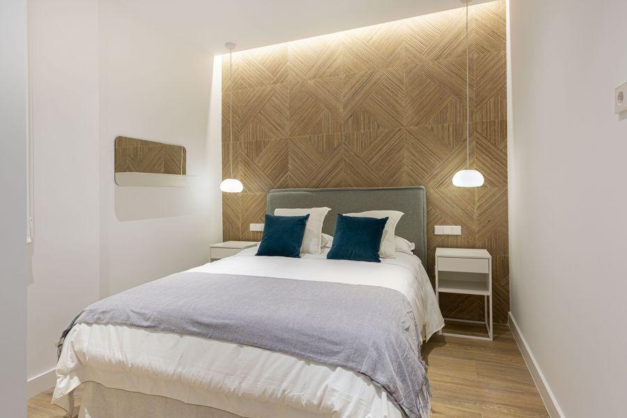 Dormitorio moderno con papel pintado en el frente y tira de led en el techo.
