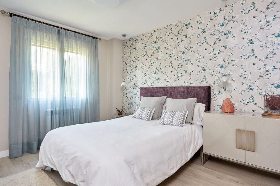 Dormitorio romántico con papel pintado de flores en el cabecero
