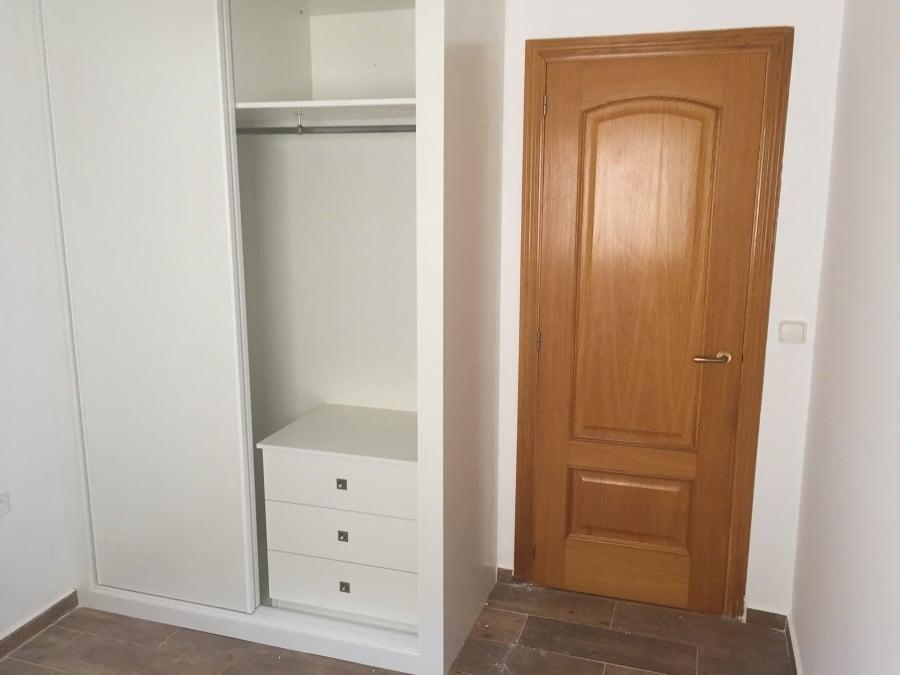 El armario tiene 2 puertas correderas de melamina  blanca.  ( no es lacado).