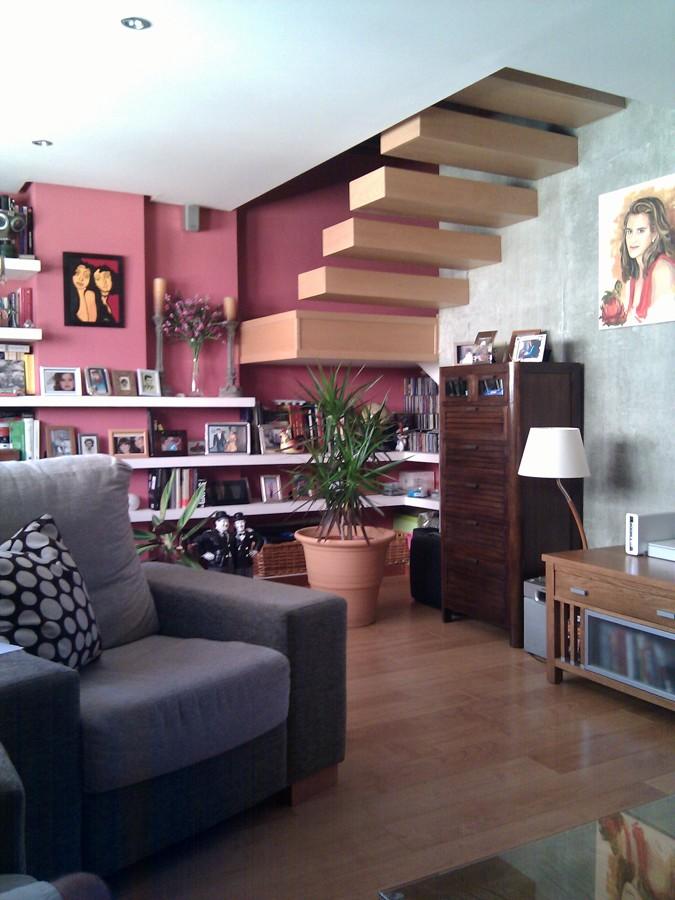 Escalera en Madera sobre pared de hormigón visto.