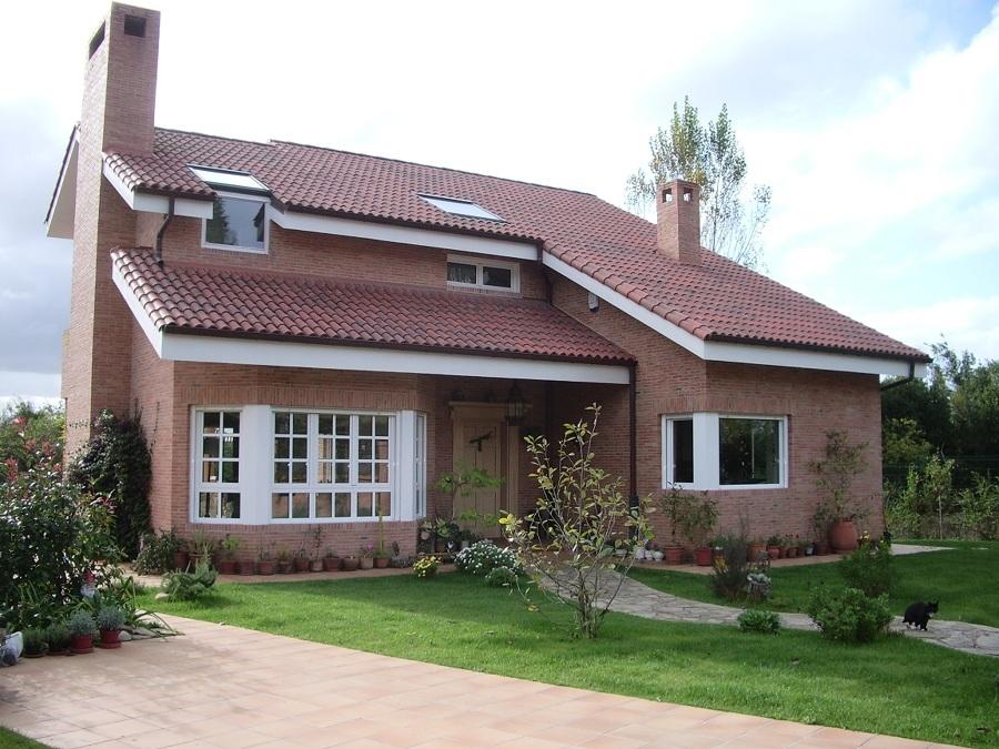 Fachada de ladrillo visto, cubierta,  jardín y aceras