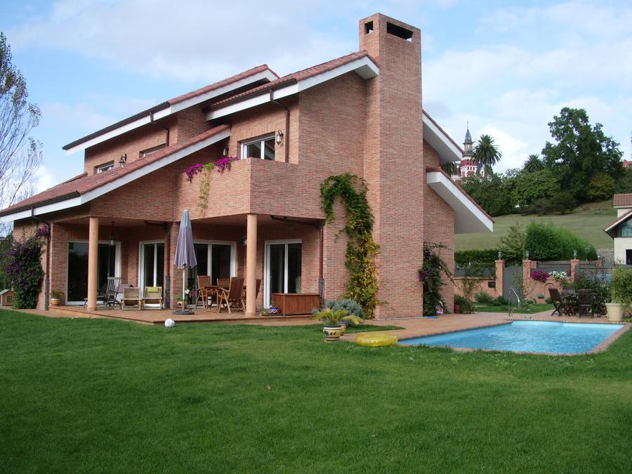 Fachada de ladrillo visto, jardín y piscina