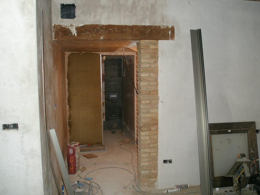 falcado de viga de madera sobre viga de hierro, anediendo un pilar de cara vista en la entrada