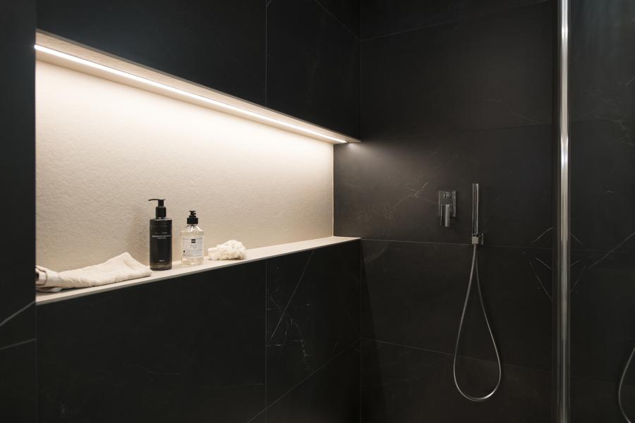 Hornacina en blanco que contrasta con el negro de la baldosa de la ducha