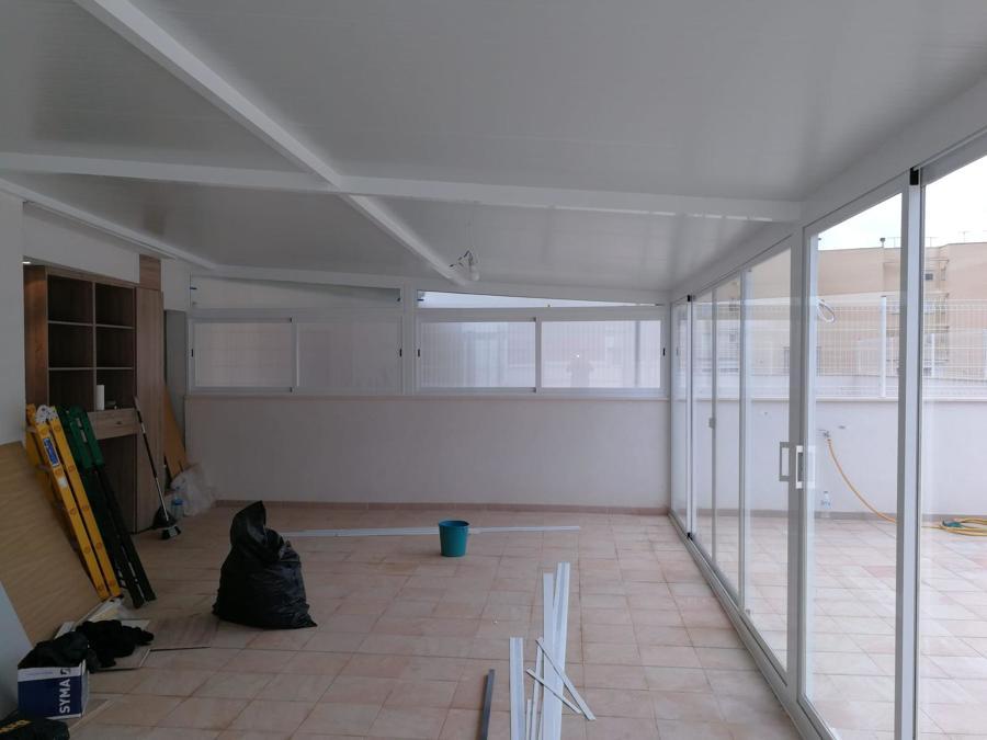 Instalación de carpintería de aluminio y techo de panel sandwich con aislamiento