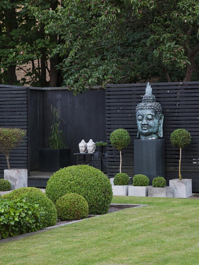 jardín con césped y esculturas zen