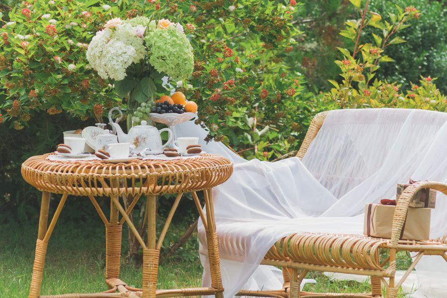Jardín con muebles de mimbre y desayuno en la mesa