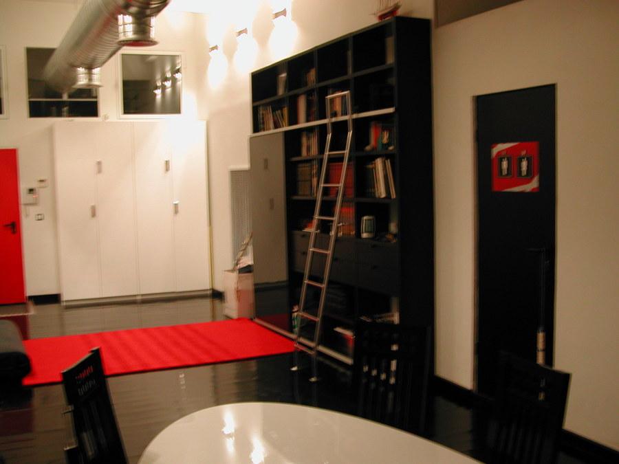librería frente al futón y puerta de acceso al baño de cortesía