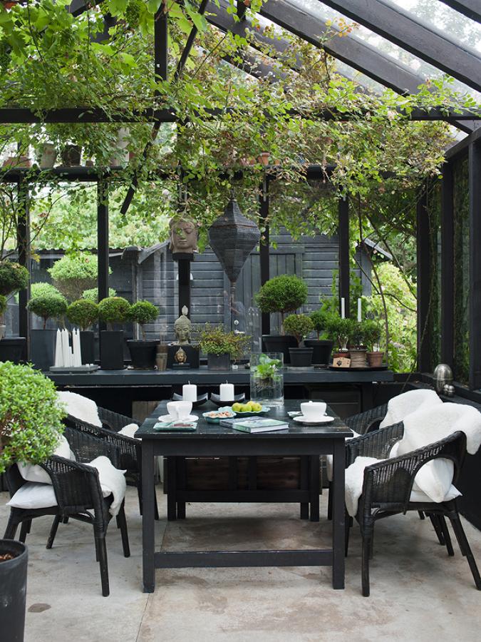mesa en jardín cerrado con figuras zen y plantas