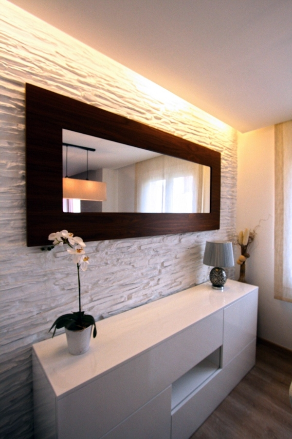 Mueble auxiliar del comedor con pared decorativa e iluminación indirecta.