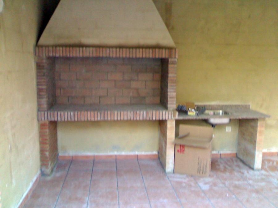 Paellero realizado en el interior del porche, con apoyos de ladrillo ...