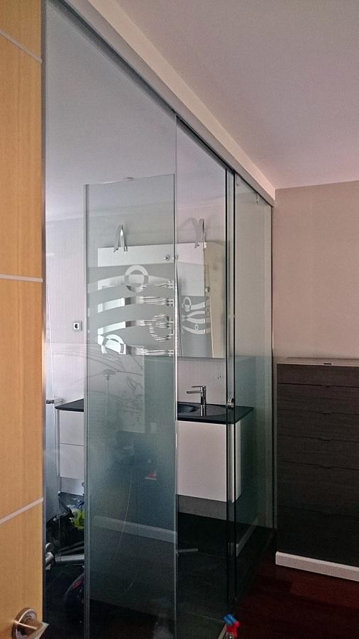 Pared divisoria  ,con paneles y Puerta corredera  de Crista Securit del baño y la habitación  .