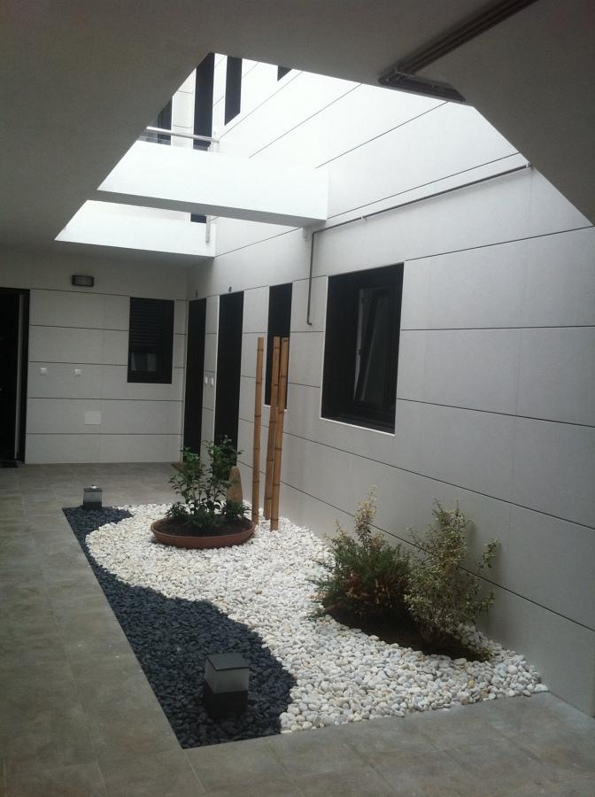 Foto patio interior de acceso a viviendas de eduardo goy for Piedras blancas para patio