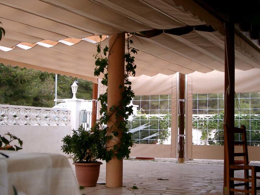 Pérgola de madera con toldo y cortinas tensadas