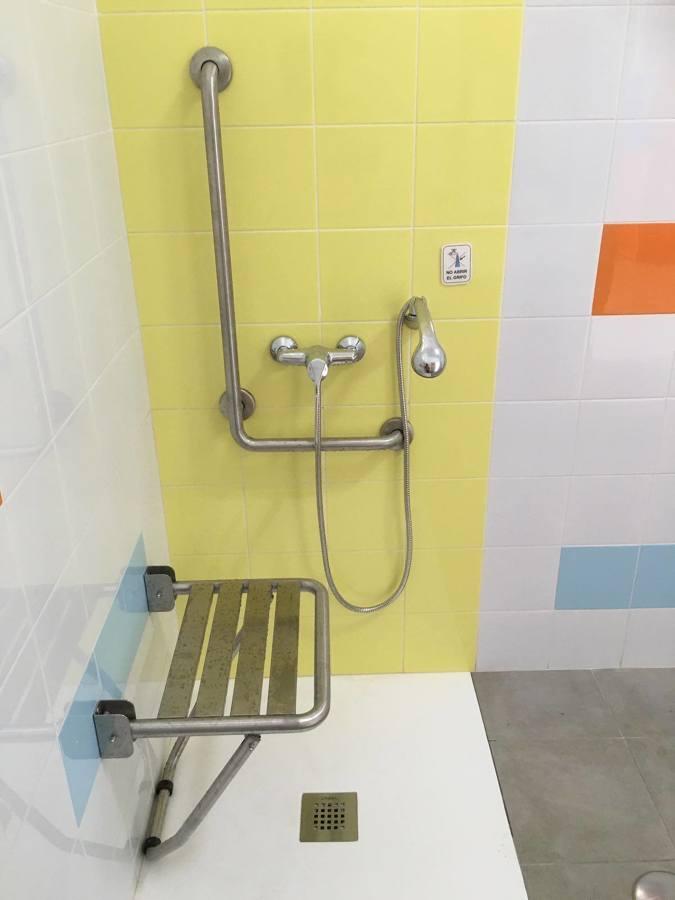 Plato de ducha extraplano con banco y barras de apoyo para discapacitados.