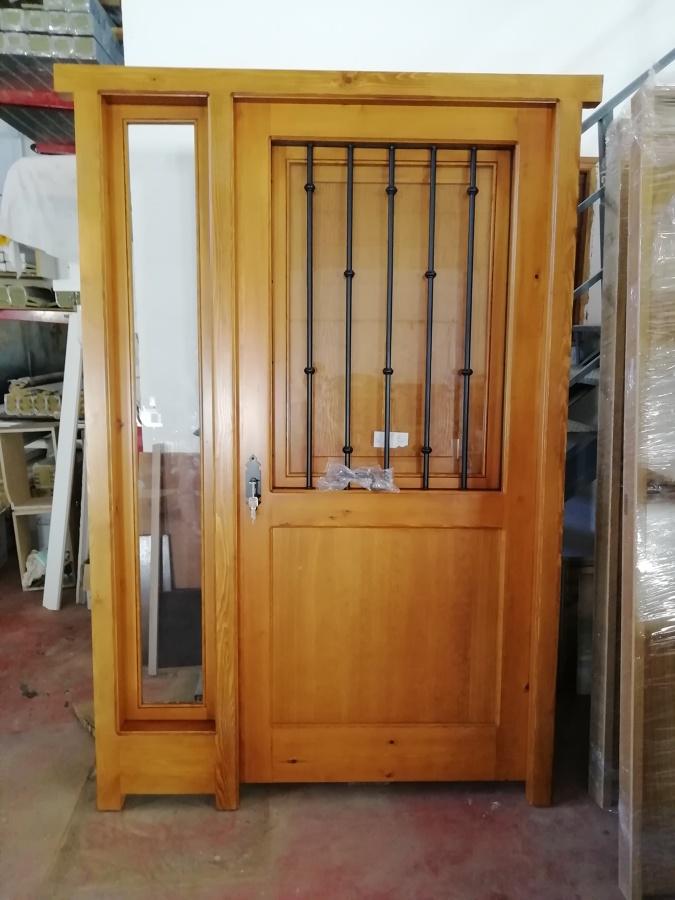 Puerta calle con ventanillo y reja de forja
