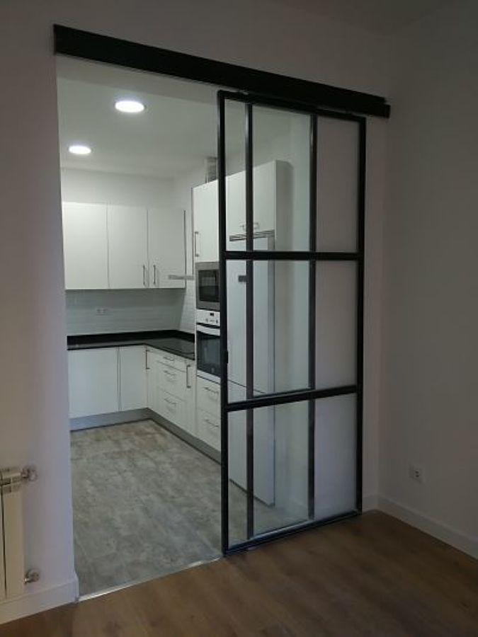 Puerta corredera de cerrajería negra y vidrio