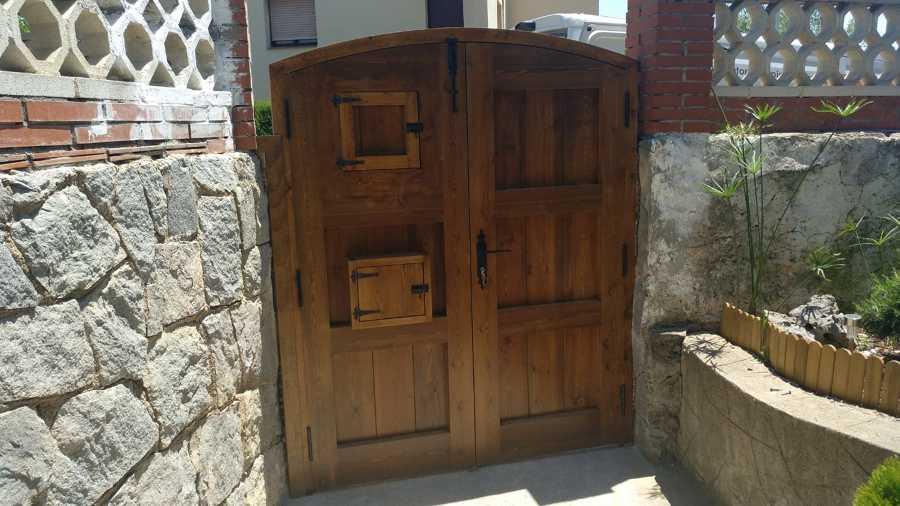 Puerta de madera con forma curva y buzon cartas