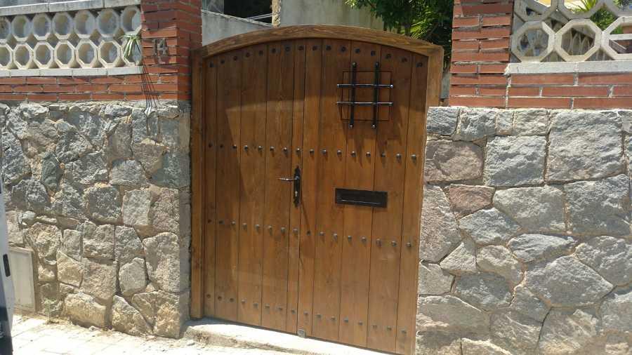 Puerta rústica de madera, completada con tachones y reja