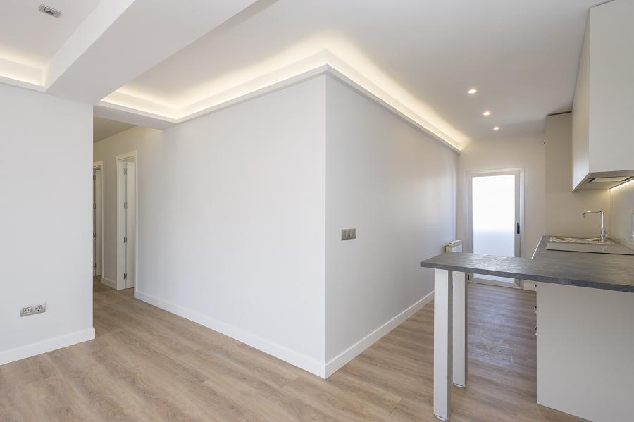 cocina abierta, salón y pasillo conectados por la iluminación LED en el techo