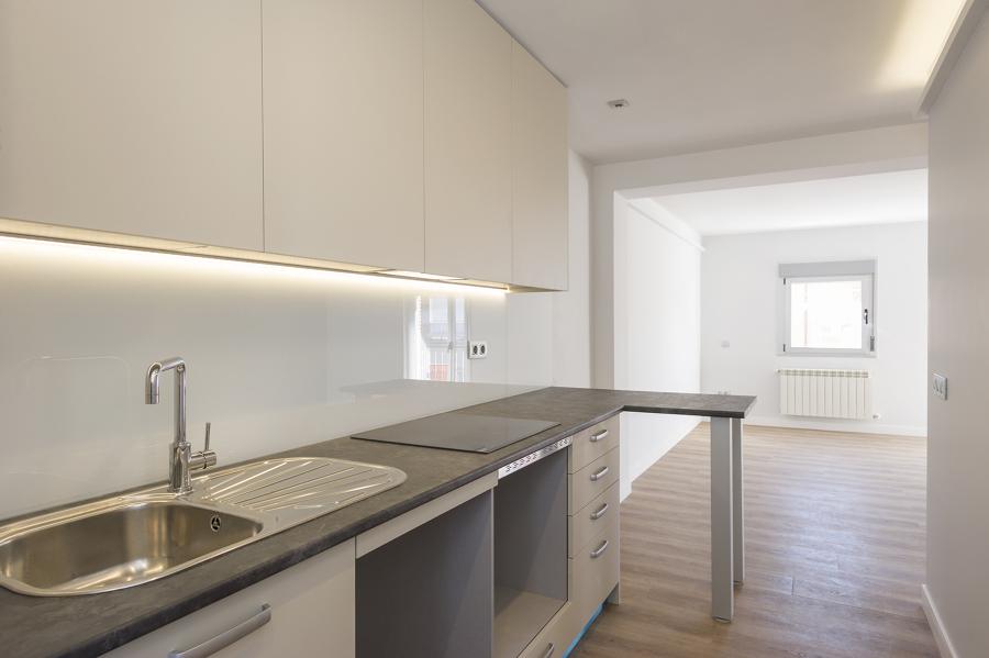 Cocina abierta al salón con encimera de mármol en L e iluminación LED