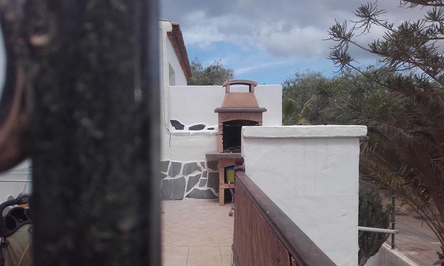 Reparacion pared barbacoa del vecino adornada con piedras